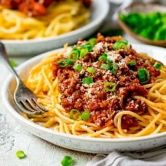 A bowl of pasta with many different types of food on a plate  Description automatically generated